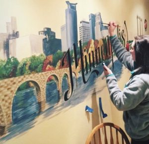 Maddy painting a mural of the stone arch bridge in Minneapolis, MN